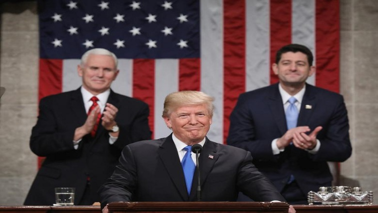President Donald J. Trump stands at the podium as Vice President Mike Pence and Speaker of the House US Rep. Paul Ryan look on during his first State of the Union address.