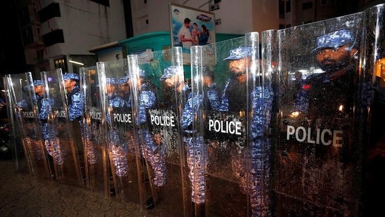 Maldivian police stand guard on a main street during a protest.