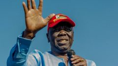 Picture of Morgan Tsvangirai wearing a red cap and blue shirt and holding a microphone.