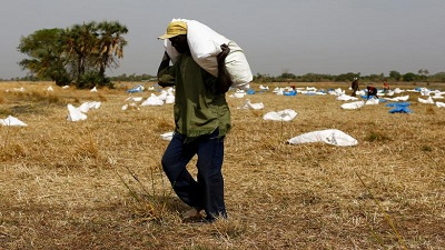 A man collects sacks of food from a dry river bed after a United Nations World Food Programme (WFP) airdrop close to Rubkuai village in Unity State, northern South Sudan