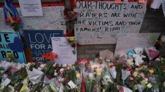 Flowers and messages are left by mourners at a makeshift memorial a day after a van struck multiple people along a major intersection in north Toronto.