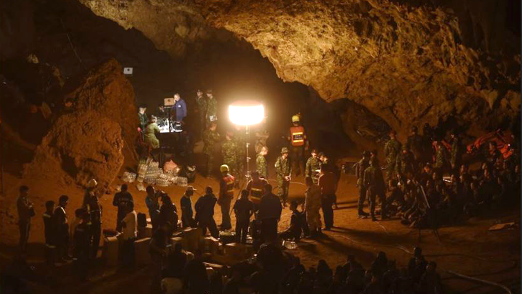 People outside a cave.