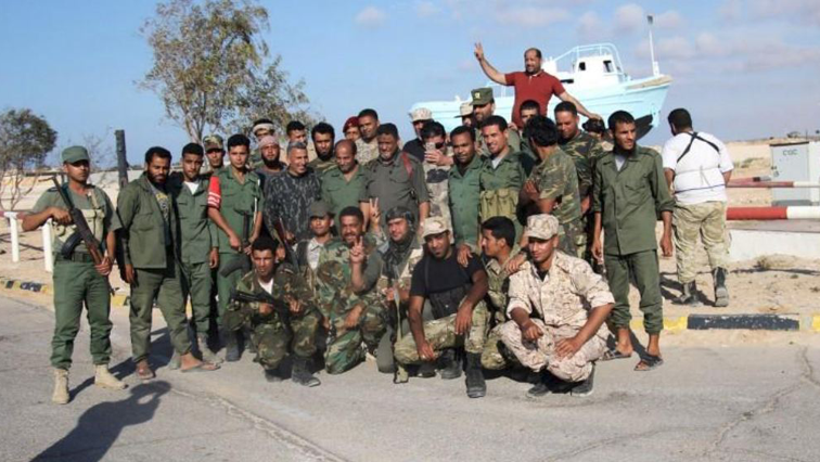 Members of the Libyan National Army poses for a photo next to Sidra oil port in Ras Lanuf, Libya.