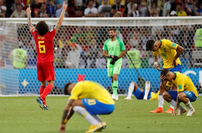 Belgium's Axel Witsel celebrates at the end of the match as Brazil's Philippe Coutinho, Roberto Firmino and team mates look dejected.