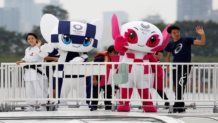 Tokyo 2020 Olympic Games mascot Miraitowa and Paralympic mascot Someity wave with Japan's Paralympic long-jumper Hajimu Ashida and karateka Kiyo Shimkizu atop a cruise ship during their water parade in Tokyo