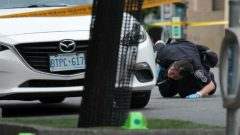 A police officer looks for evidence under a car while investigating a mass shooting on Danforth Avenue in Toronto, Canada.