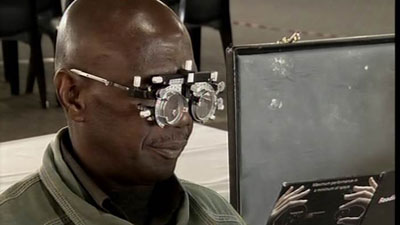 An elderly man testing eyes.