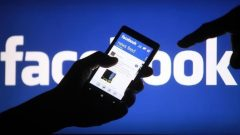 Cellphone on hand, Facebook logo on the background