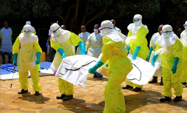 Congolese officials and the World Health Organisation officials wear protective suits