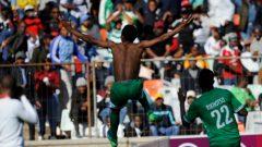 Bongani Sam takes off his shirt, celebrating.