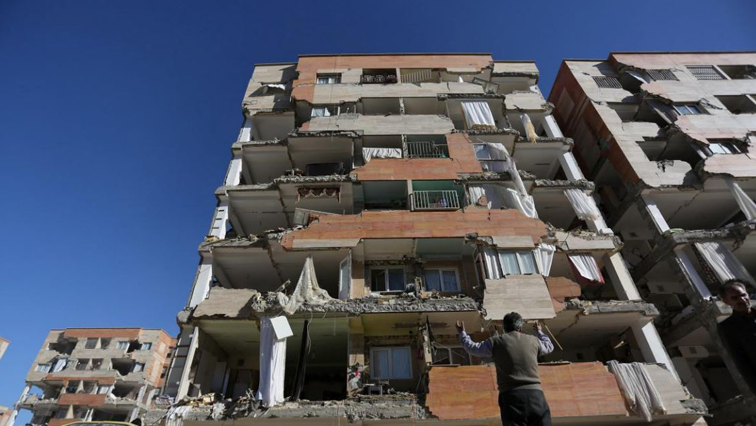 A man reacts as he looks at a damaged building.