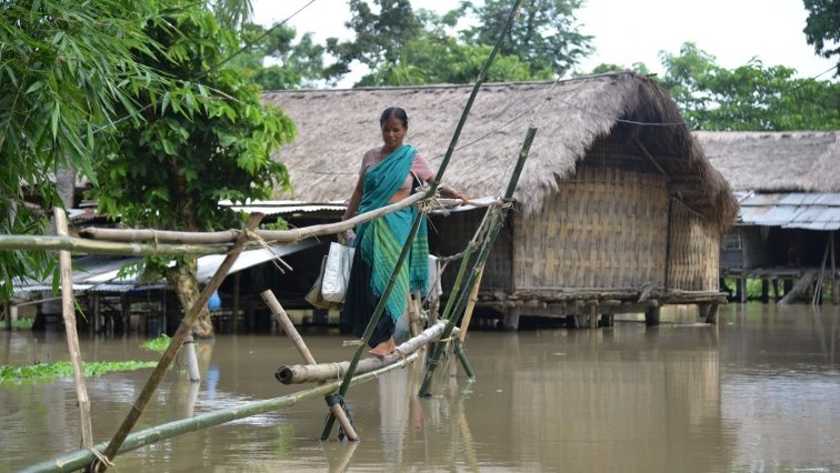 A woman on a makeshift bridge over flood waters