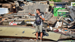 A foreign tourists stands near damaged buildings.