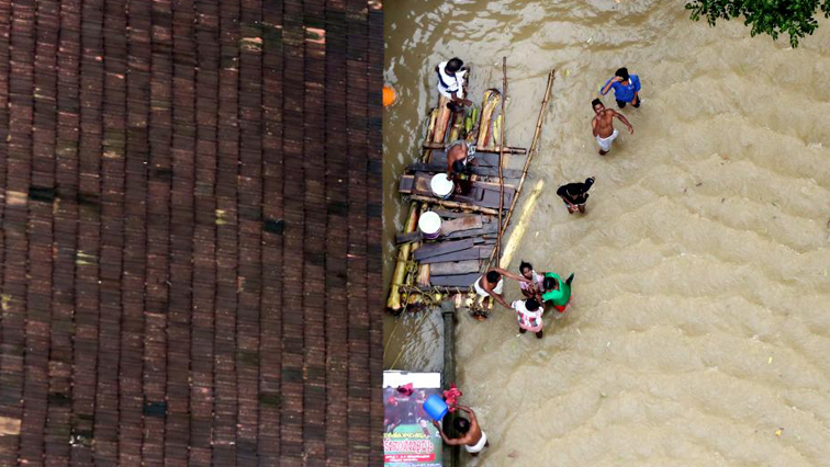 People wait for aid next to a makeshift raft at a flooded area in Kerala,