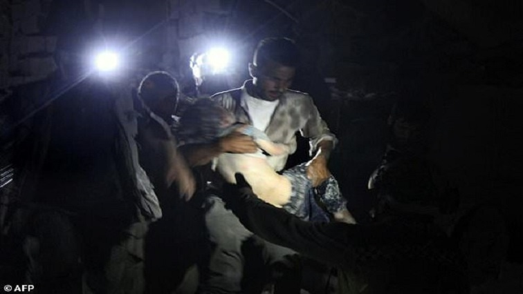 Adults lifting a child out of the rubble
