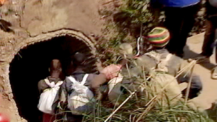Illegal miners in front of a mine opening