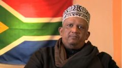 Moulana Ighsaan Hendricks sitting in front of the SA flag