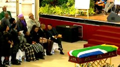 Winston Ntshona's coffin draped with South African flag lies in front of mourners