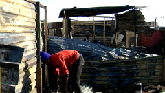 A man sifting through shack remains