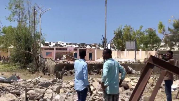 People look at debris at the site of a blast in Mogadishu