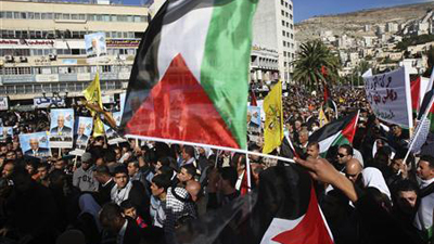 Palestinians waving their red, white, green and black flag