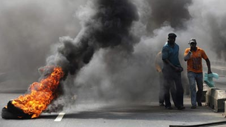 The road is blocked with burning tyres and barricaded with stones.