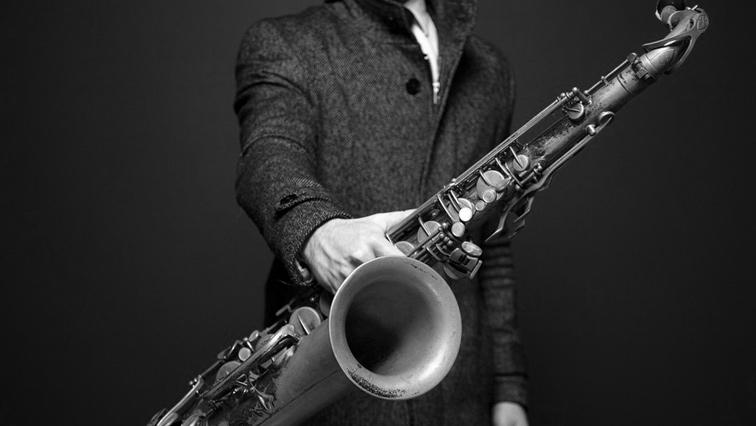 A person holding a saxophone