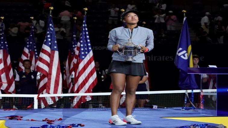 NaomiOsaka holding US Open trophy.