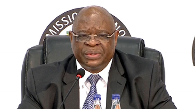 Deputy Chief Justice Raymond Zondo with a mic in front of him.