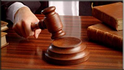 A hand holding a court gavel