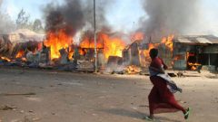 shacks burning and a woman walking by.