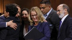 Christine Blasey Ford (C) is surrounded by her attorney Michael Bromwich (R), supporters and security agents