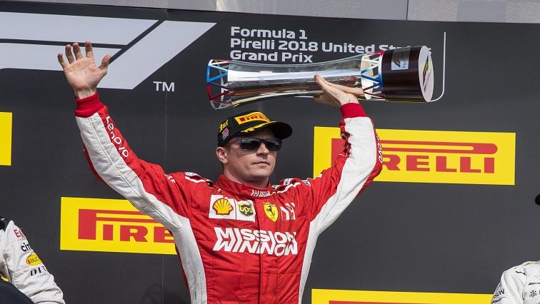 Ferrari driver Kimi Raikkonen celebrating with a trophy
