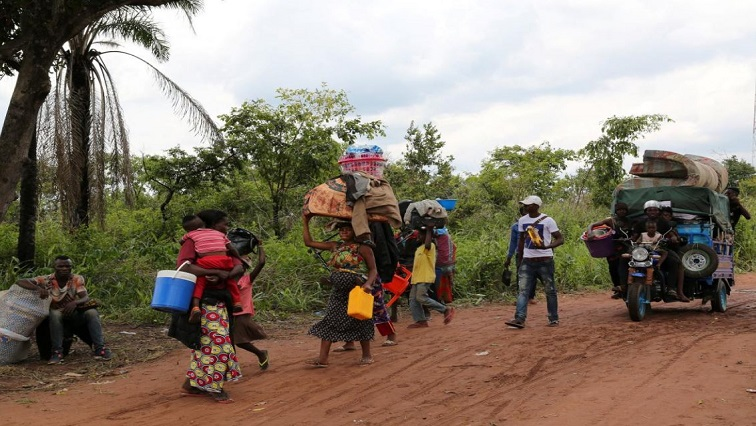 Congolese Migrants caring household belongings.