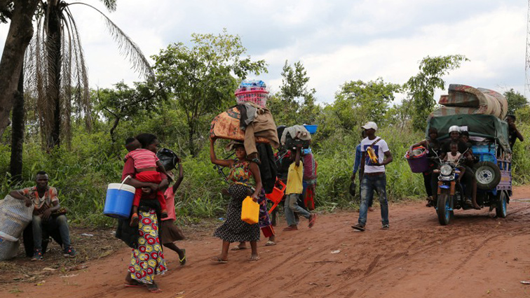 People walking with their belongings on a dirt road