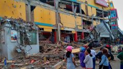 Residents stand in front of a damaged shopping mall after an earthquake hit Palu