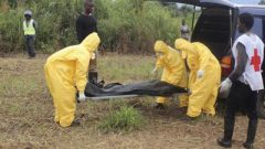 Health officials carrying a dead body of a person who died of Ebola.