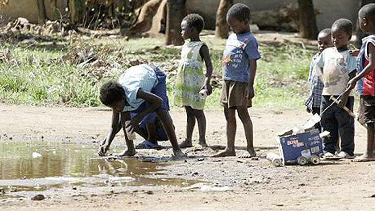 Chidren drinking water from river