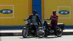 Men on motorbikes in front of MTN in Nigeria.