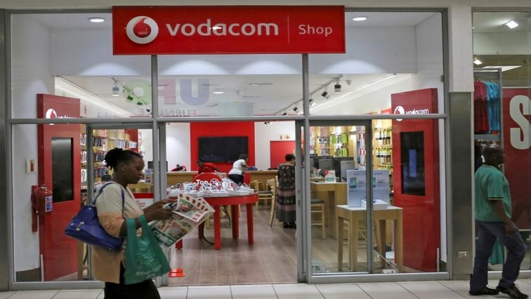 A shopper walks past a Vodacom shop in Johannesburg February 4, 2015.