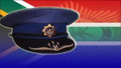 Police hat behind South African flag