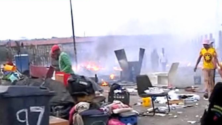 Alex residents with their possessions outside burned shacks.