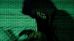 A man holds a laptop computer as cyber code is projected on him in this illustration picture taken on May 13, 2017. Capitalizing on spying tools believed to have been developed by the U.S. National Security Agency, hackers staged a cyber assault with a self-spreading malware that has infected tens of thousands of computers in nearly 100 countries.