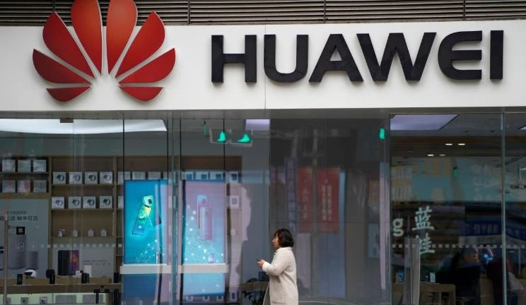 A woman walks by a Huawei logo at a shopping mall in Shanghai, China.