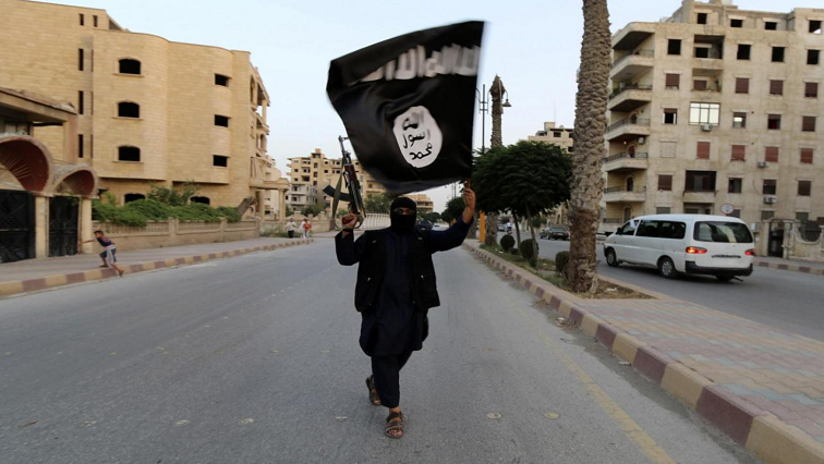 Man with covered face carrying Islamic State flag and a rifle.