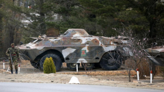 Defence Force vehicle and a soldier holding a weapon.