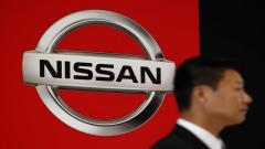 A man standing next to Nissan logo