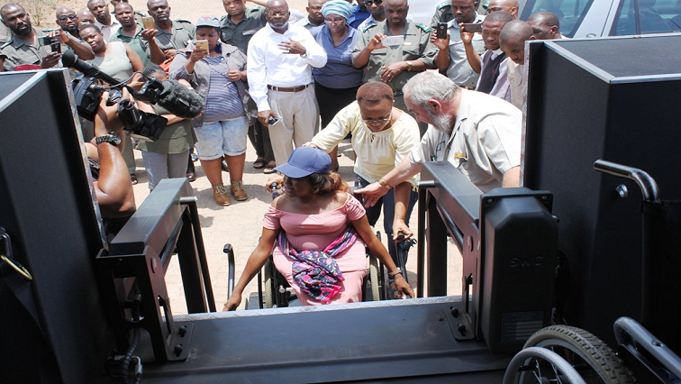 Woman on a wheelchair assisted to get on a game drive vehicle.
