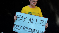 A person living with albinism protesting against discrimination.