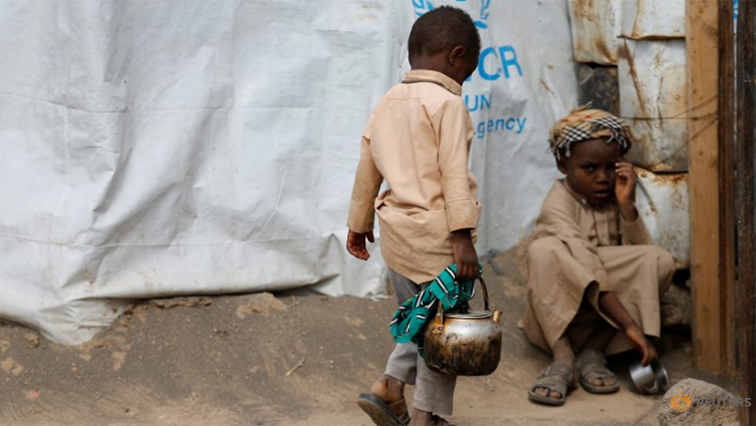 A child carries a kettle while another sits on the ground